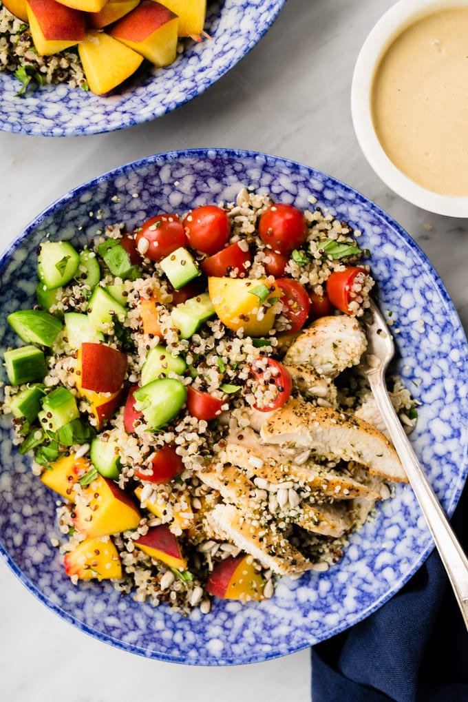 Healthy and protein packed summer quinoa salad with chicken, peaches, cucumbers, and tomatoes and a side of sunflower seed butter dressing.