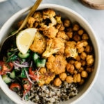 Shawarma cauliflower over quinoa with crispy chick peas and tomato cucumber salad for a vegan shawarma buddha bowl.