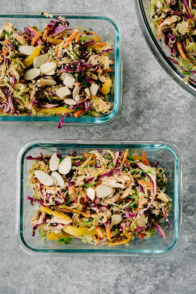 Meal prep containers filled with healthy chicken salad, made with no mayo almond butter dressing, poached chicken, bell peppers, carrots, cabbage, brussels sprouts, sesame seeds, and almonds.