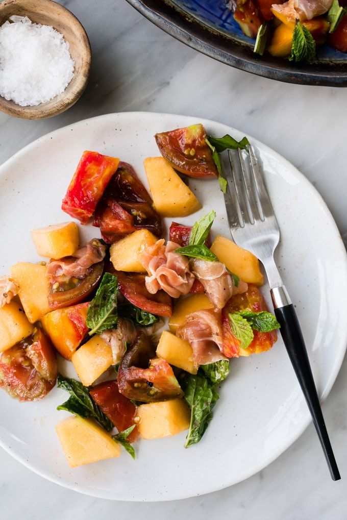 Melon salad with prosciutto, tomato, mint, and basil on a white plate with a fork.