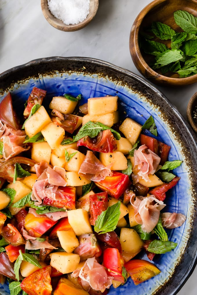 Melon salad with prosciutto, tomato, mint, and basil on a marble table.