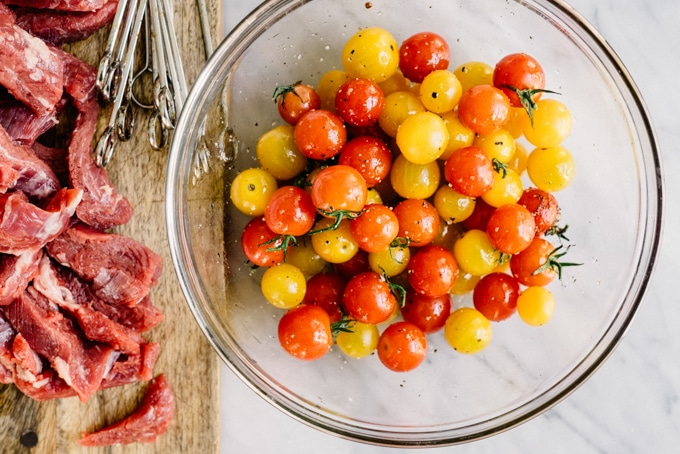 Thin sliced of flank steak on a cutting board next to a bowl of cherry tomatoes tossed with olive oil, salt, and pepper.