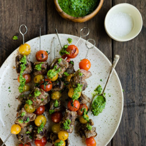 Grilled tomato and steak skewers on a speckled platter, drizzled with paleo parsley pesto.