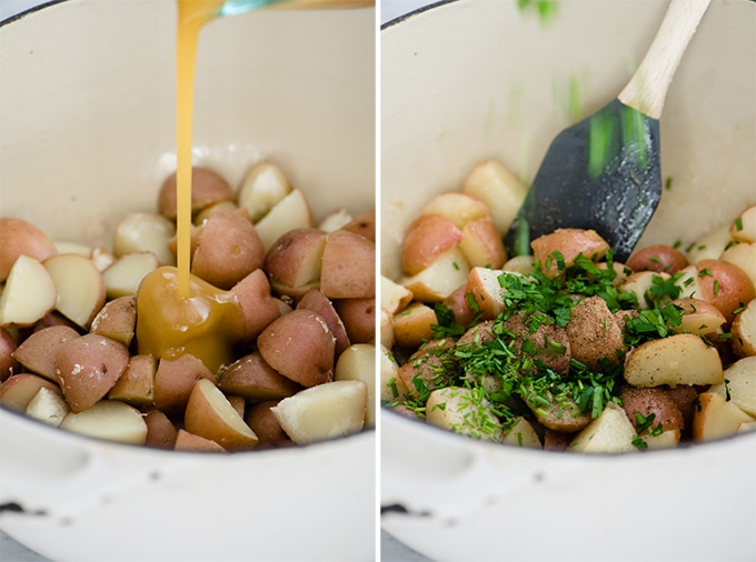 Vinaigrette and fresh herbs being added to cooked potatoes in a white dutch oven.