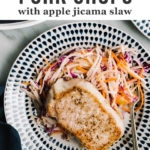 Tender thick cut oven roasted pork chops over apple jicama slaw on a blue and white plate with a navy linen napkin.