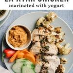 A plate of yogurt marinated za'atar chicken with roasted cauliflower, muhammara dipping sauce, and sliced raw vegetables.