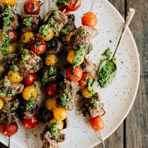 A platter of tomato and steak skewers drizzled with dairy free pesto on a wood background.