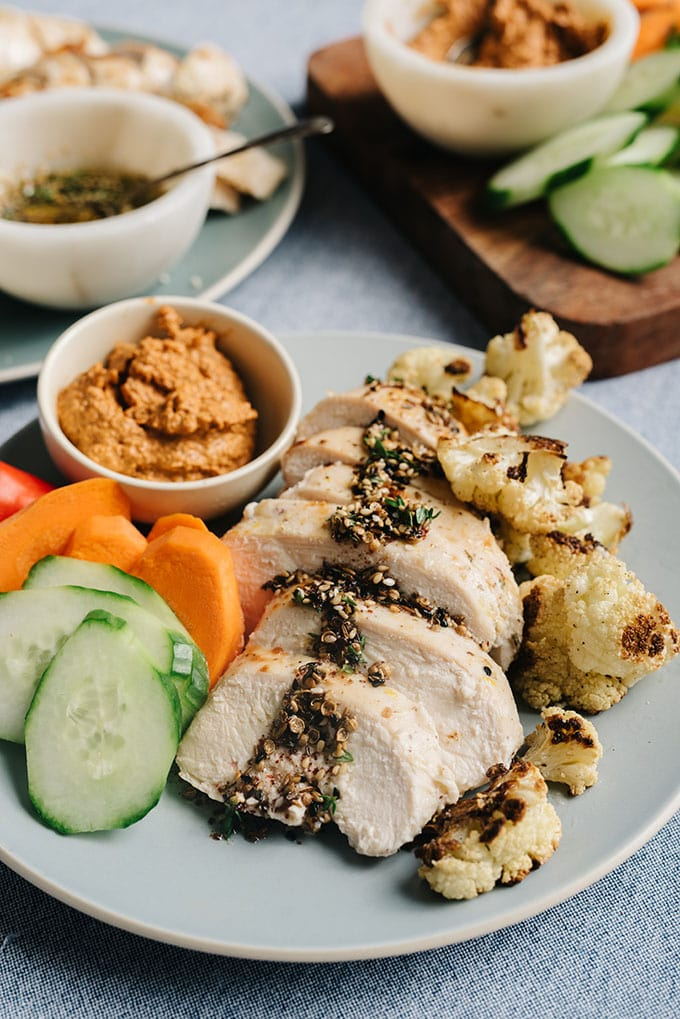 A plate of sliced za'atar marinated baked chicken drizzled with zaatar oil, served with fresh and roasted vegetables.