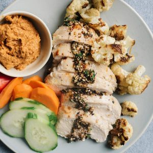 A plate of baked zaatar chicken with roasted cauliflower, muhammara dipping sauce, and sliced raw vegetables.