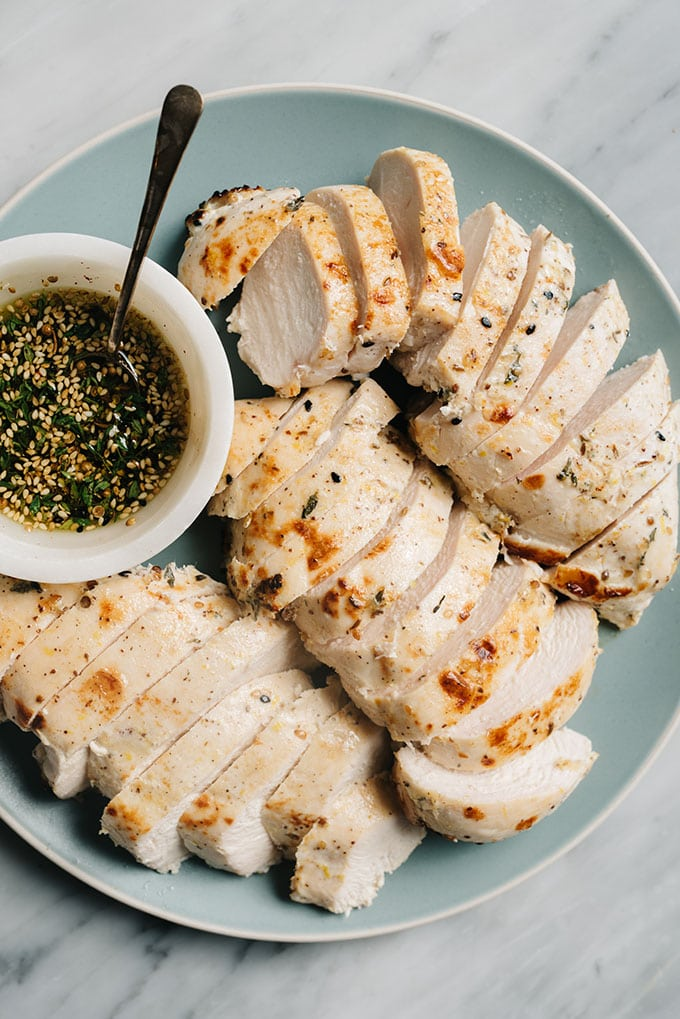 A platter of sliced za'atar chicken breasts with a small bowl of zaatar spice mixed with olive oil.