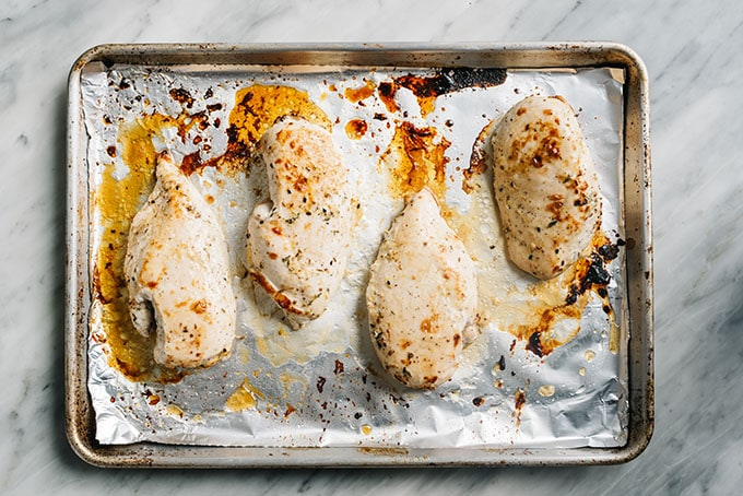Fresh from the oven baked za'atar and yogurt marinated chicken breasts on a baking sheet.