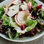 Butter lettuce and radicchio tossed salad on a small white plate drizzled with champagne vinaigrette.