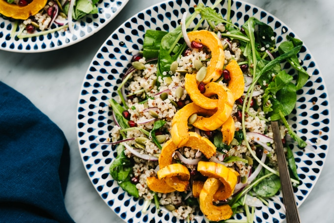 Gluten free delicata squash salad on a plate with arugula, quinoa, pomegranates, and creamy maple dressing.