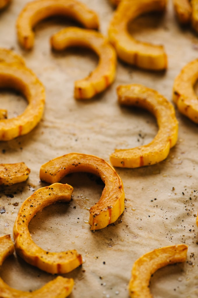 Roasted delicata squash on a baking sheet.