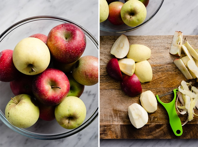 A large glass bowl filled with a variety of apples, and sliced and cored apples on a cutting board.