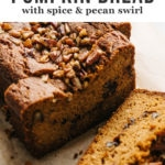 Several slices of paleo pumpkin bread with spiced coconut sugar swirl and pecans on a cutting board.