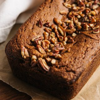 A loaf of paleo pumpkin bread topped with pecans on a cutting board.