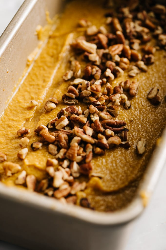 Paleo pumpkin cake batter in a bread pan sprinkled with chopped pecans.