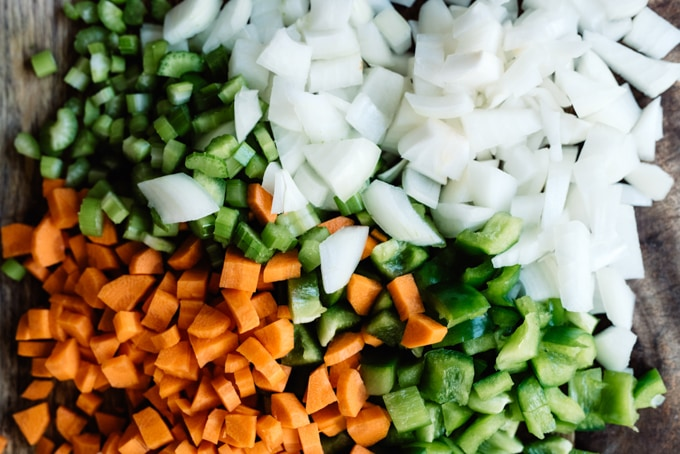 Diced mire poix - onions, carrots, and celery - on a cutting board.