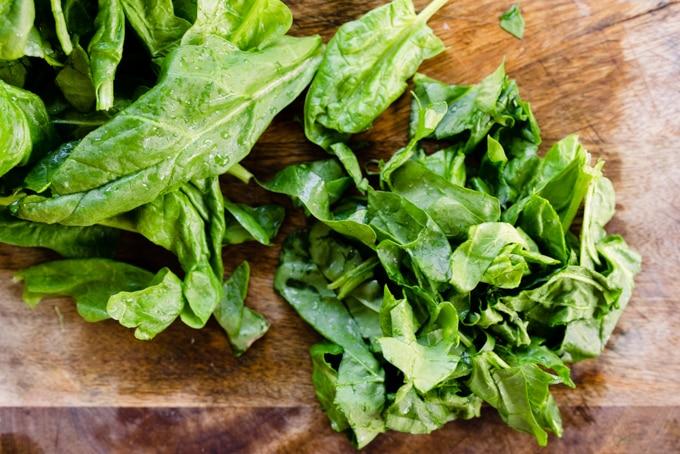 Chopped fresh spinach on a cutting board.