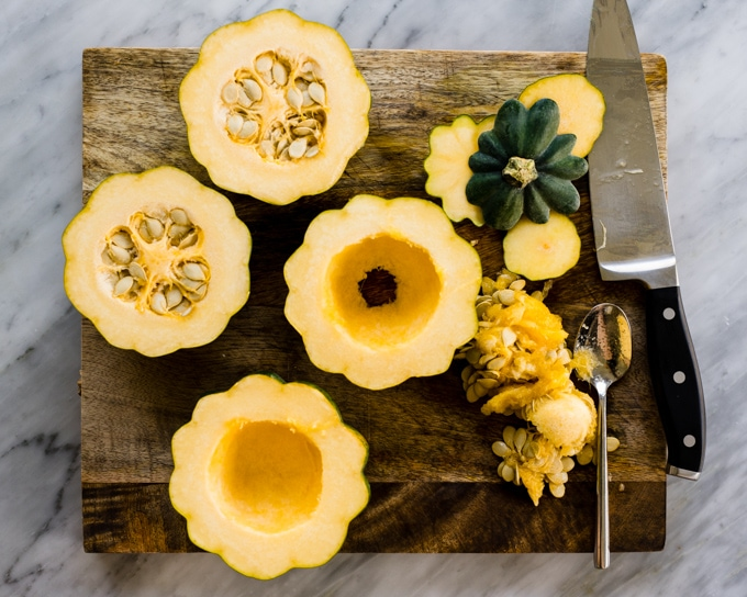 Acorn squash sliced in half with seeds scooped out.