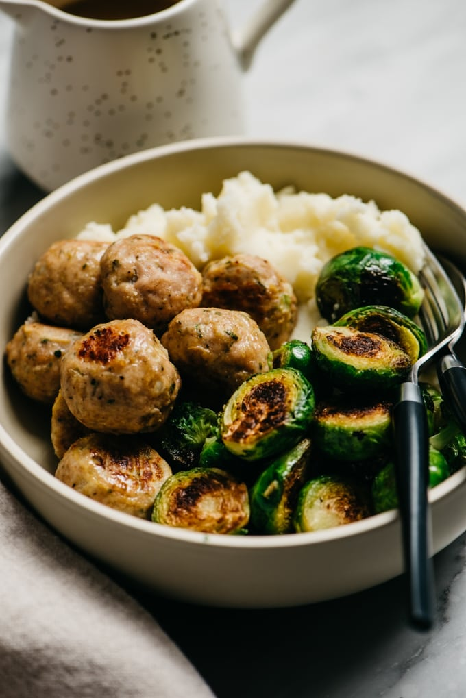 Baked turkey meatballs with mashed potatoes and roasted brussels sprouts in a bowl.