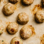 Easy baked turkey meatballs fresh from the oven on a baking sheet lined with parchment paper.