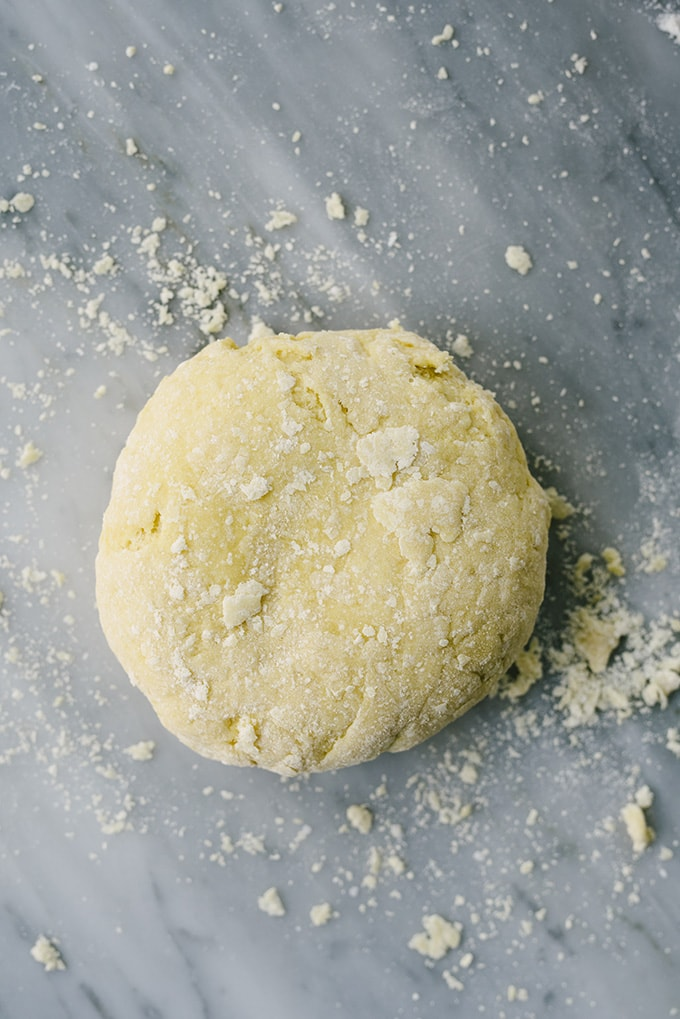 A ball of chrusciki dough on a marble surface.