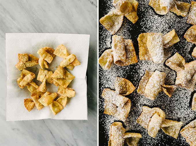 Freshly fried chrusciki cookies draining on a paper towel lined plate, and chrusciki on a baking sheet dusted with powdered sugar.