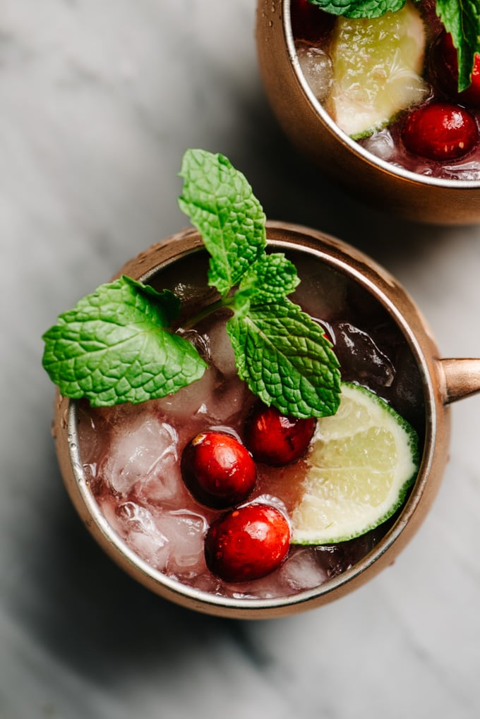 An overhead view of a cranberry moscow mule cocktail on a marble table.