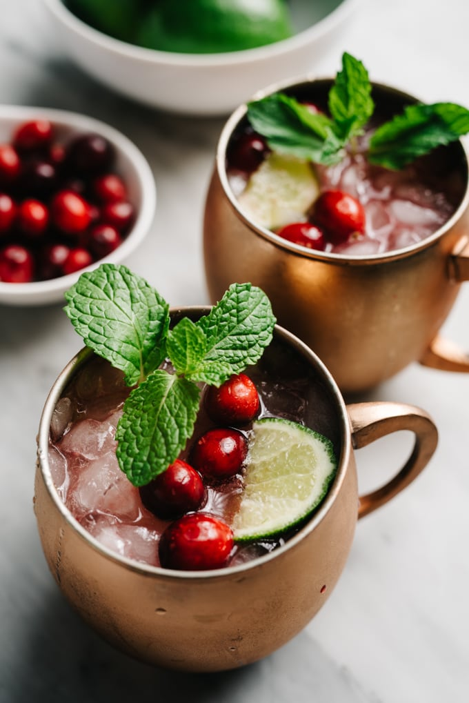 Two cranberry moscow mule cocktails on a marble table with a small bowl of fresh cranberries.