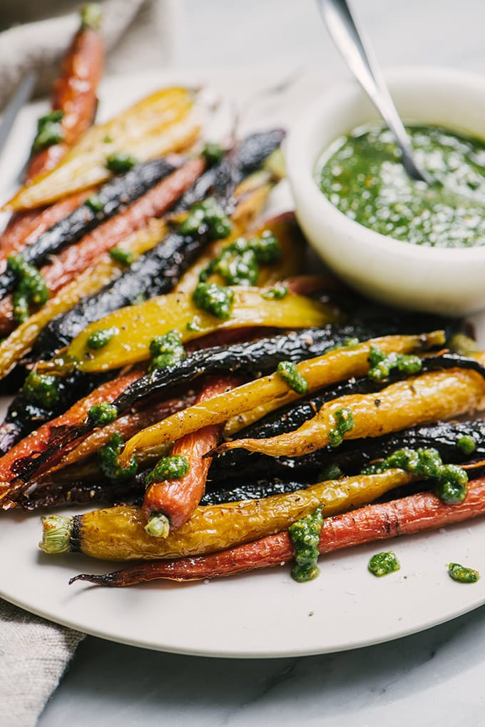 A white plate filled with honey roasted carrots drizzled with carrot green pesto.