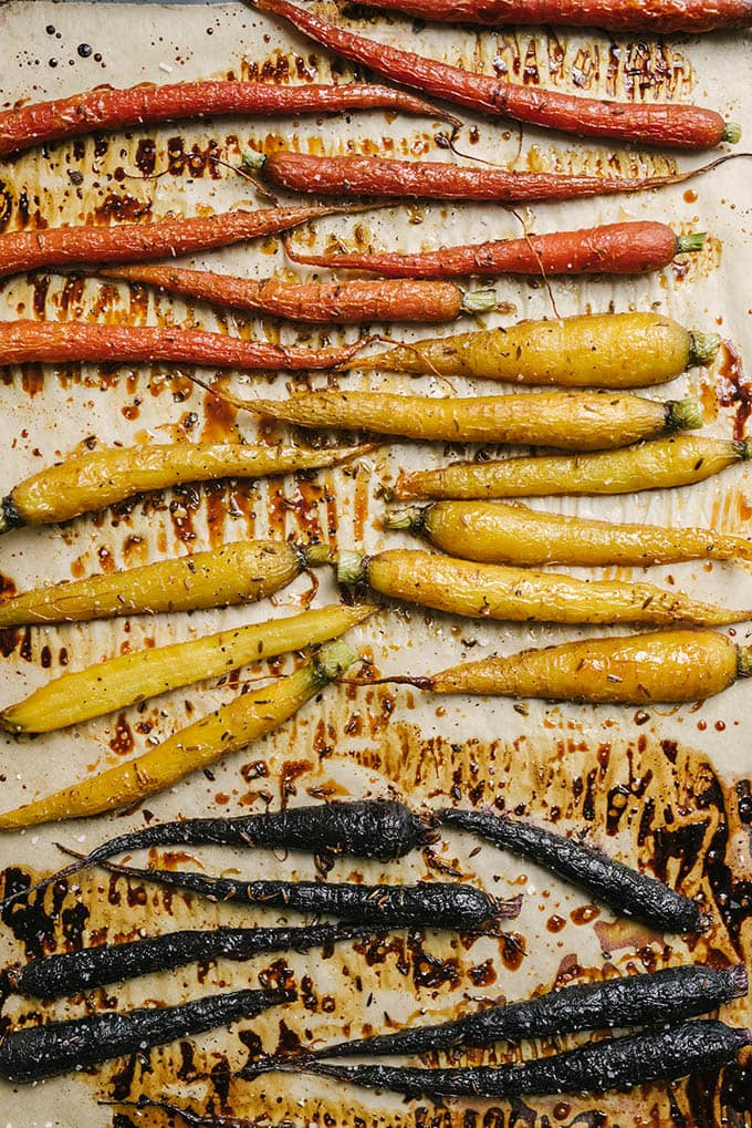Tri-color honey roasted carrots on a baking sheet lined with parchment paper.