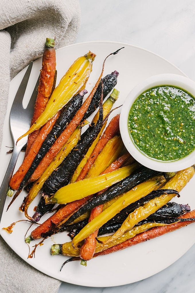 A plate of tricolor honey roasted carrots with cumin seeds on a white plate with a small bowl of carrot green pesto.