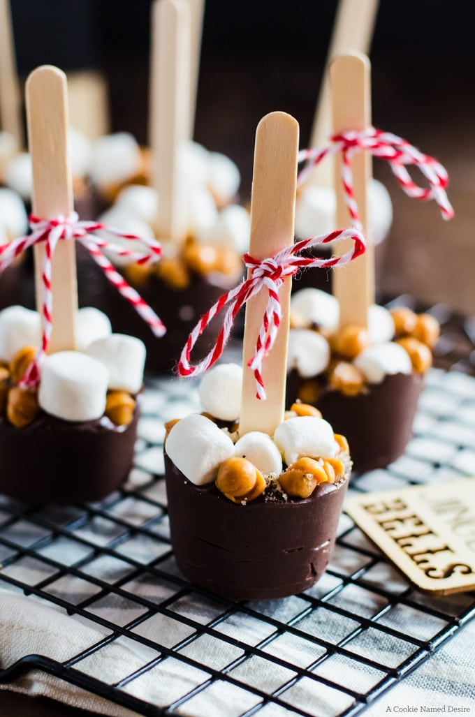 Homemade hot chocolate on a stick edible Christmas gifts on a wire rack.