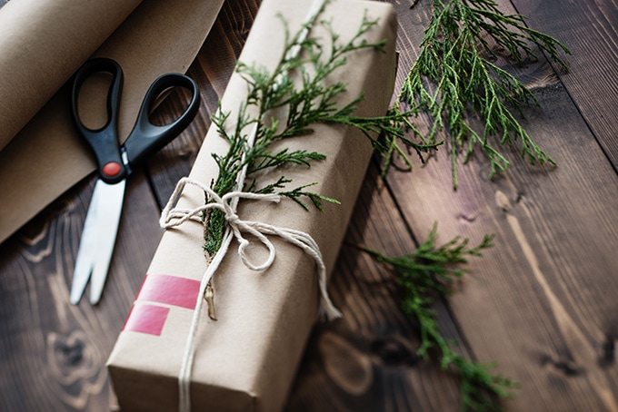 An edible Christmas gift wrapped in brown kraft paper with washi tape and greenery.