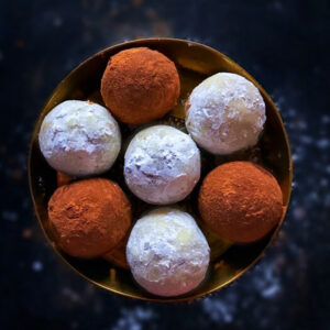 Gingerbread cookie truffles in a gold bowl on a chalkboard background.