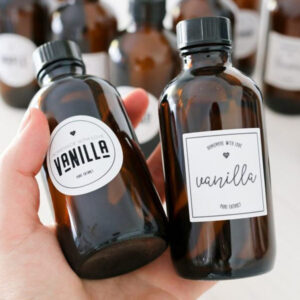 A woman's hand holding two jars of homemade Instant Pot Vanilla Extract.