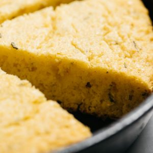 Healthy rosemary cornbread baked in a cast iron skillet fresh from the oven.