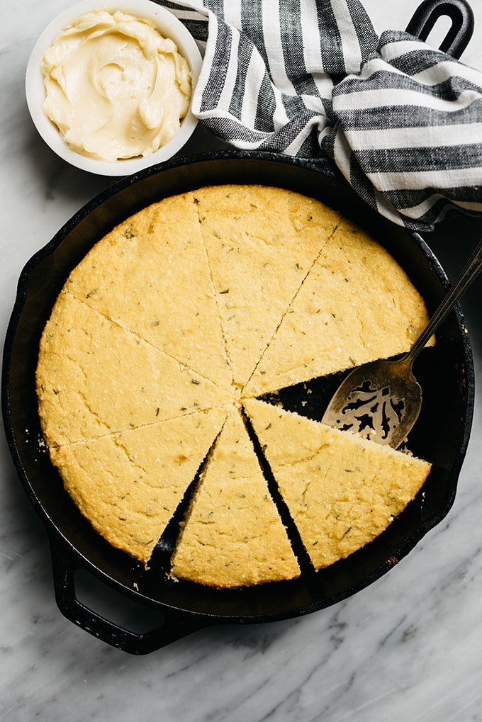 Healthy cornbread baked in a cast iron skillet on a marble table with a small dish of honeybutter.
