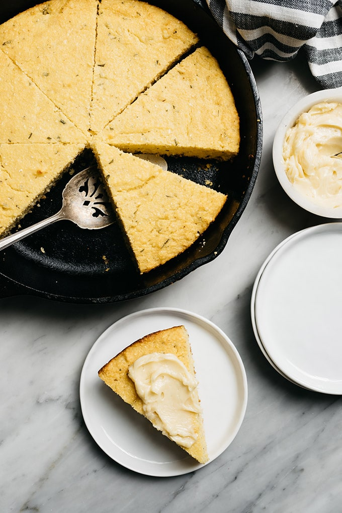 Healthy cornbread with rosemary in a cast iron skillet, and a piece of cornbread on a plate with honey butter.