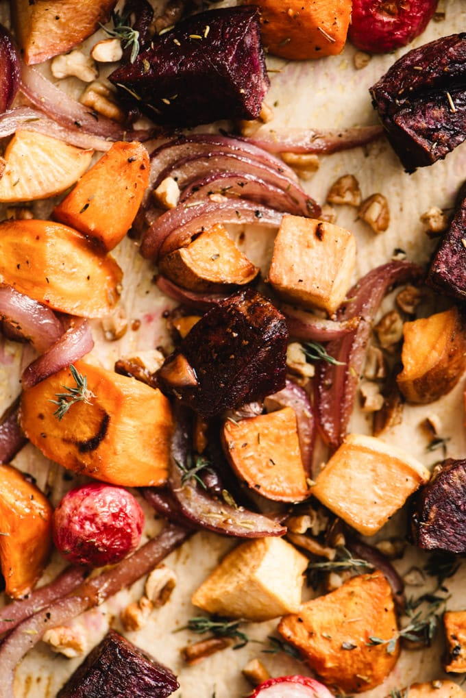 Overhead view of roasted root vegetables with maple syrup on a baking sheet.