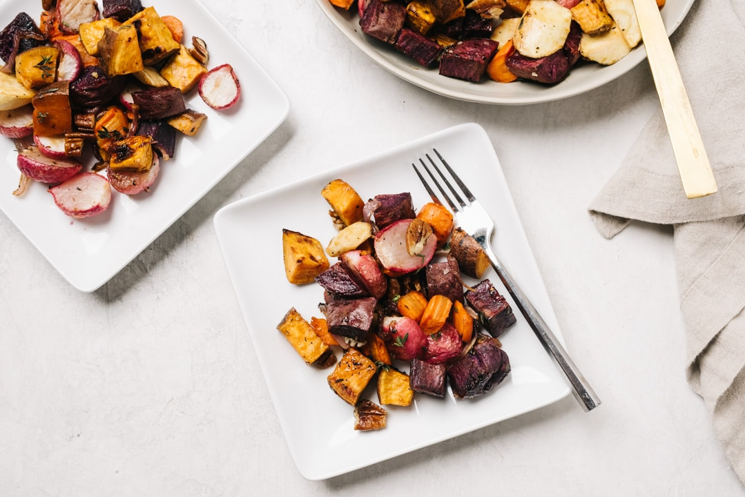 Two small square plates of maple roasted root vegetables, a large serving bowl, and a tan linen napkin on a concrete background.
