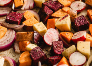 Root vegetables arranged in an even layer on a baking sheet seasoned with maple, olive oil, salt, and pepper.