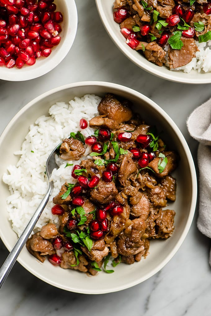 A bowl of paleo pomegranate chicken braised with walnuts and coconut milk served over white rice garnished with parsley and pomegranate seeds.