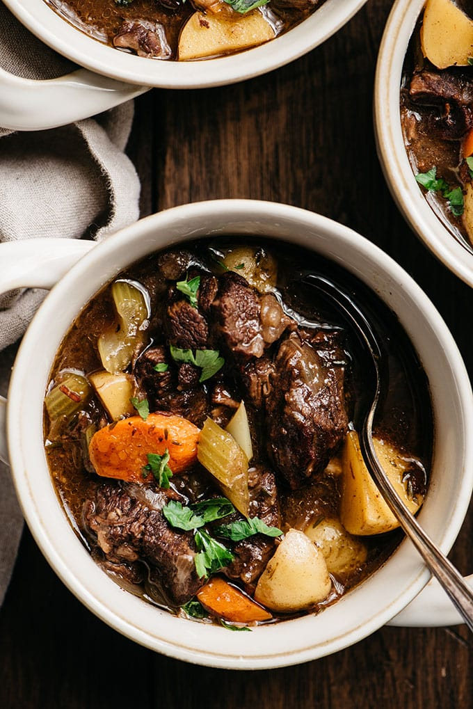 A bowl of red wine beef stew with a soup spoon and fresh parsley garnish.