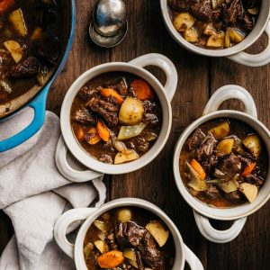Several crock bowls of dutch oven braised red wine beef stew garnished with parsley on a wood table.