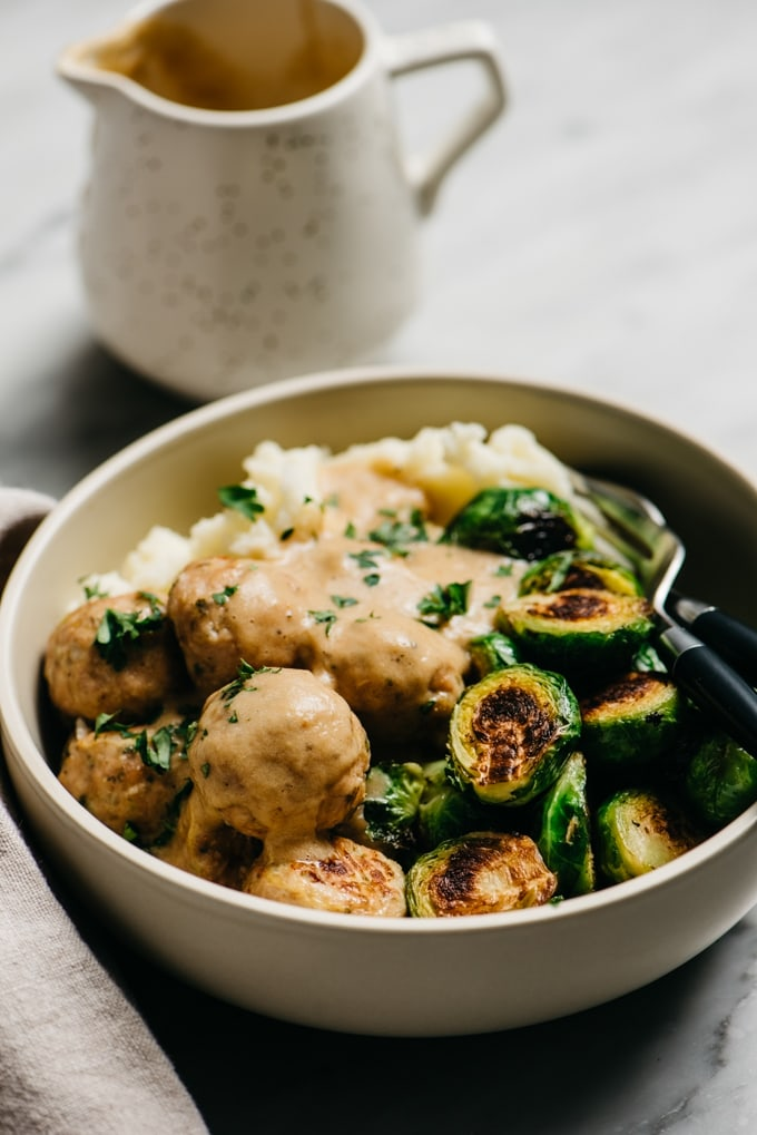 Turkey meatballs served over mashed potatoes and brussels sprouts, smothered with onion gravy, on a marble table with a tan linen napkin.