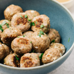 Side view, baked turkey meatballs in a blue bowl garnished with parsley.