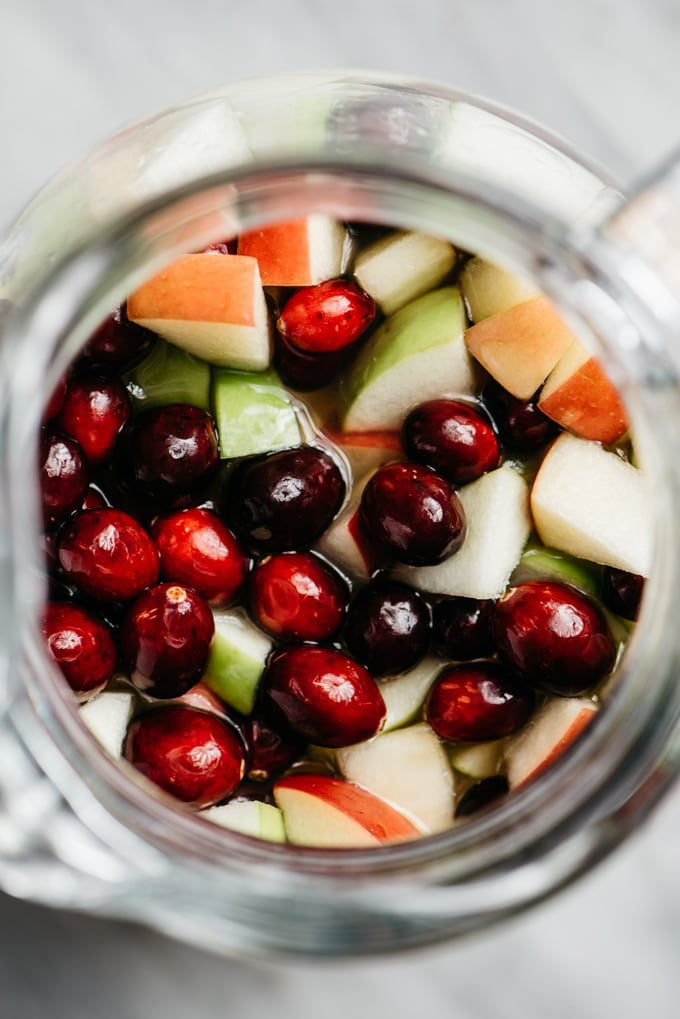 An overhead view of a pitcher filled with apple cider sangria, diced apples, and fresh cranberries.